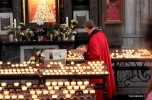 A priest lights up prayer candles